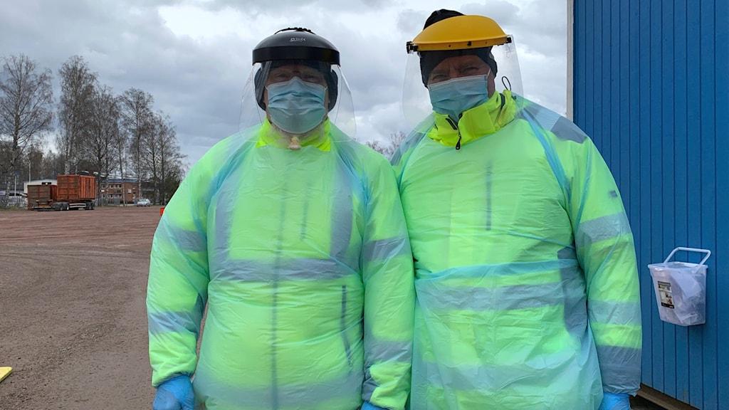 Två män i reflexkläder och skyddsutrustning.