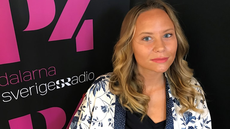 Erika Lindblom framför en vägg med P4-loggan