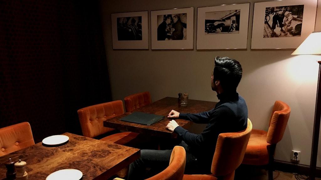 En ung man som heter Behzad sitter på en stol med ryggen mot kameran. Han sitter å tittar på tavlor på en vägg.