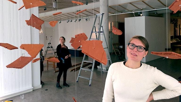 Lina Sofia Lundin står med vänster hand i midjan och tittar snett uppåt på delar av tegelstenar som hänger från taket i snören. I bakgrunden syns Henny Linn Kjellberg, konstnären som gjort verket.