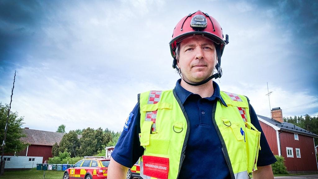 En man i brandhjälm och gul väst står framför en räddningsbil och ett rött trähus.