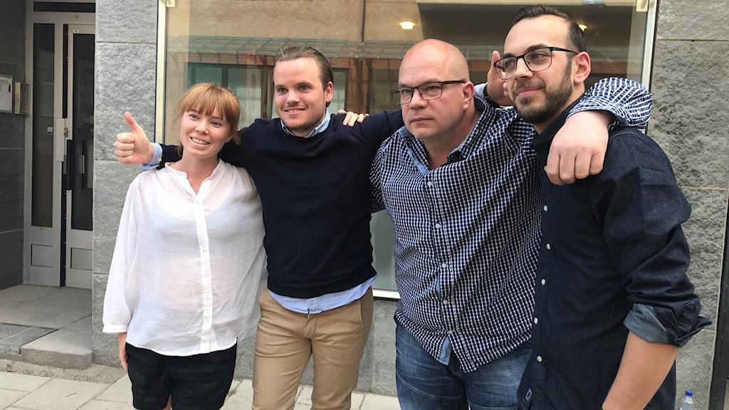 Fyra personer står och håller om varandra. En av dem gör tummen upp.