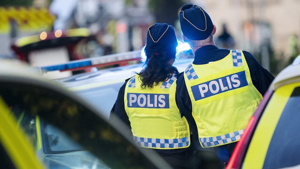 Två poliser innanför avspärrningarna i samband med en brand.