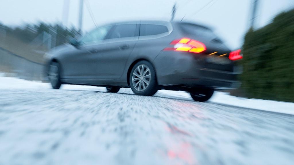 Bil som åker på en isig väg