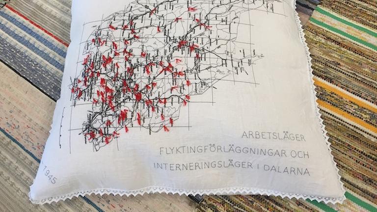 En broderad kudde är en del av en utställning om Dalarnas flyktingläger