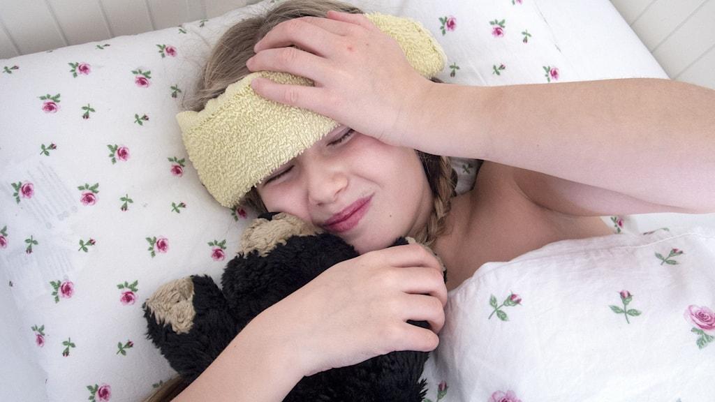 Flicka ligger i en säng och ser lidande ut, håller i en nallebjörn och har en liten handduk över pannan.