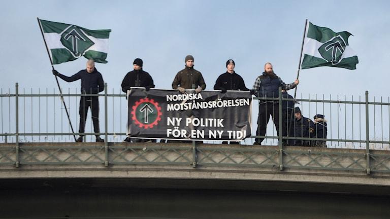 Flera medlemmar ur NMR på en bro med flaggor och banderoller