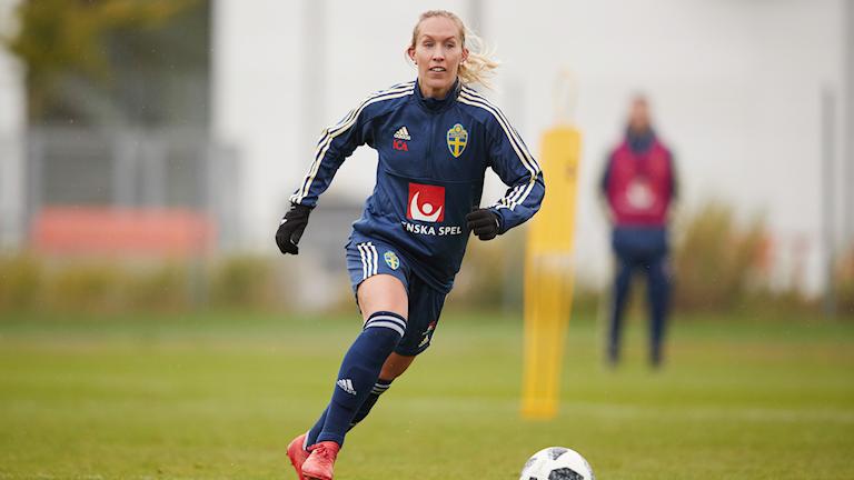 En blond kvinna i blå landslagskläder springer efter en fotboll på en plan.