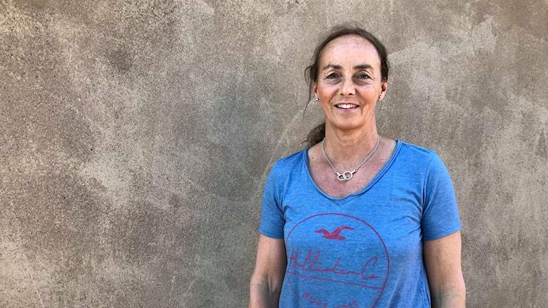 Kvinna i blå t-shirt framför brun vägg.