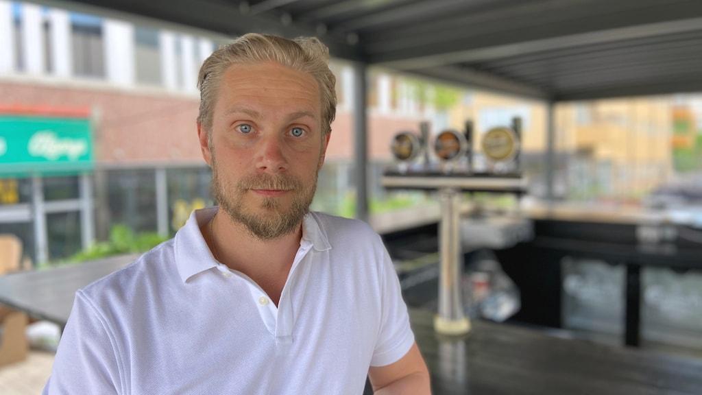 En man med ljust hår och vit t-shirt sitter vid en bardisk.