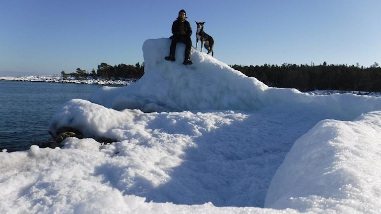 En man och en hund som sitter på ett isflak i solskenet.
