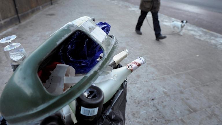 Tomflaskor i en papperskorg i stadsmiljö.