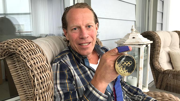 Jonas Bergqvist visar upp en medalj med OS-ringarna på.
