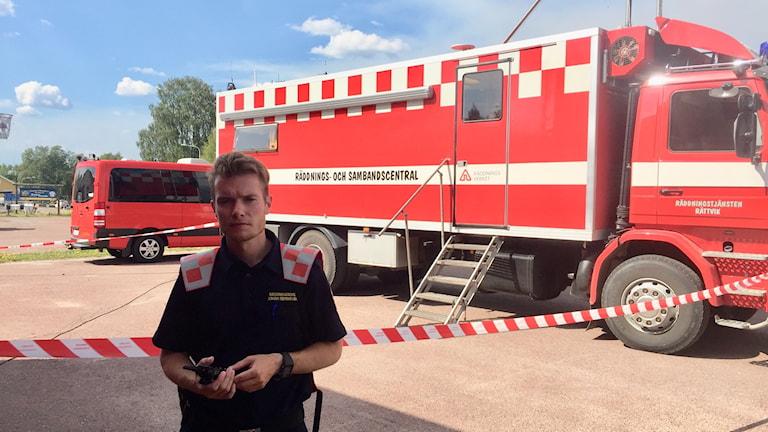 Räddningsledare Johan Szymanski framför en rödvit sambands- och ledningscentralsbuss.