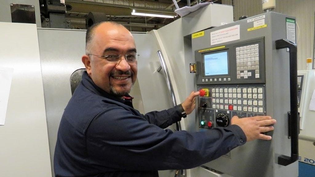 Ayad Awini står leende framför en maskin inne i en verkstadslokal.