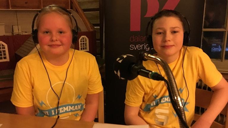 Alva Larsson och Arvid Jennessen Nordström sitter bakom ett bord framför en mikrofon och tittar in i kameran.