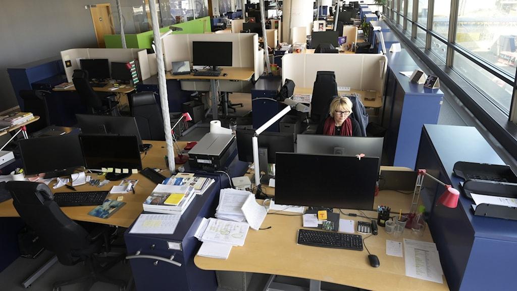 Kvinna sitter ensam på ett kontor.