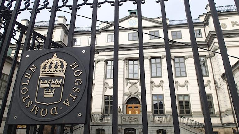 Gallergrind i metall framför en ljus byggnad. På grinden syns Högsta domstolens symbol och text.