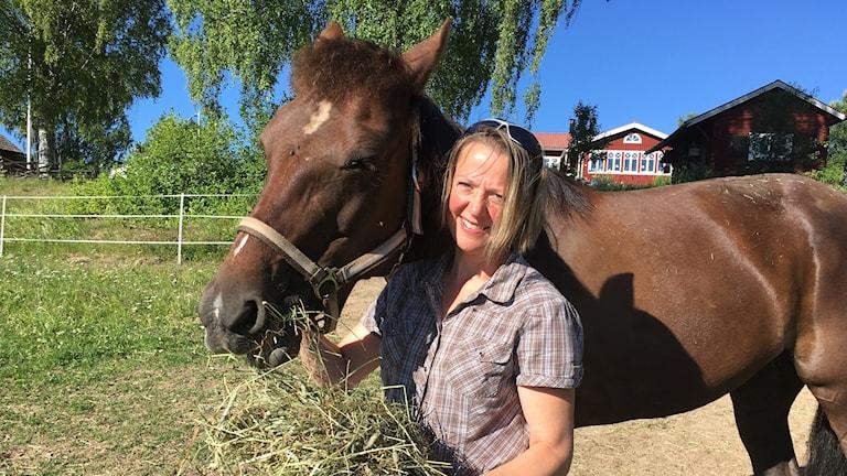 Veronika Lundeberg som är hästägare i Leksand tillsammans med en av sina hästar och lite hö.