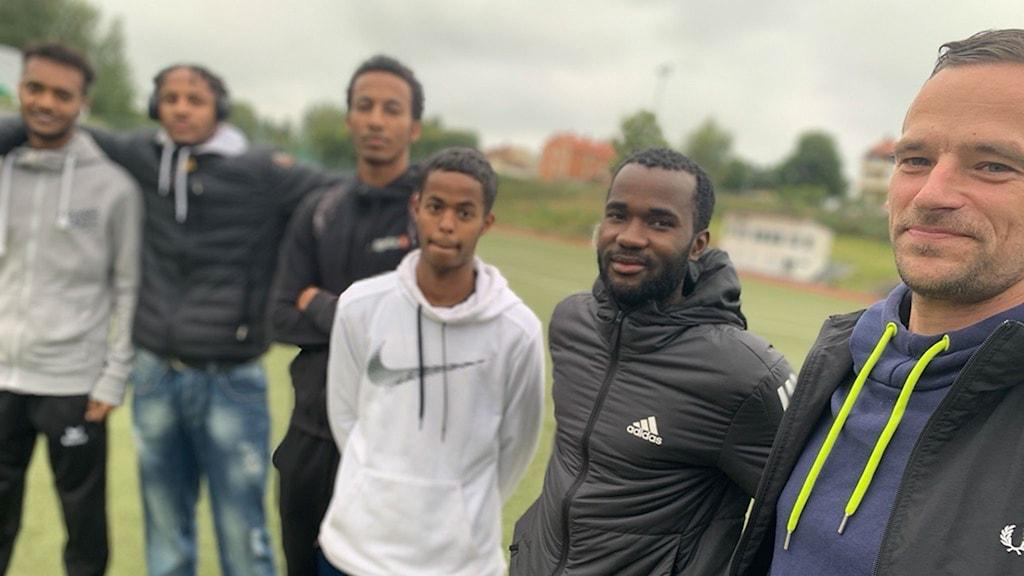 Fem mörkhyade killar och en vit man, i sportkläder på en fotbollsplan.