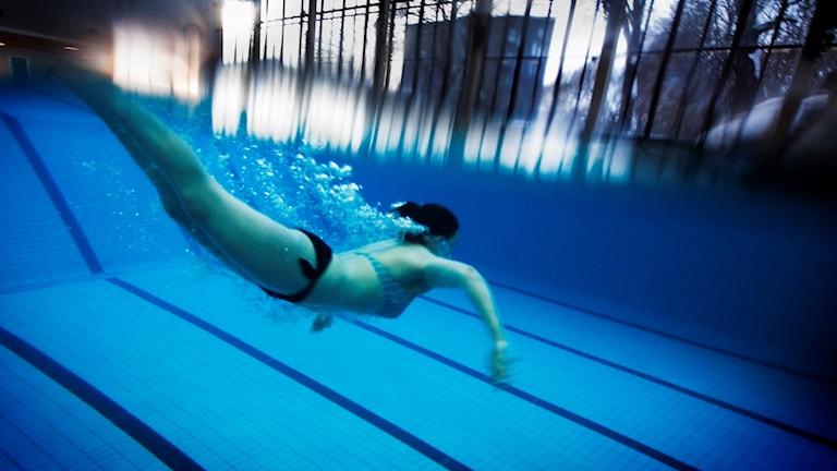 En kvinna som simmar under vattnet.