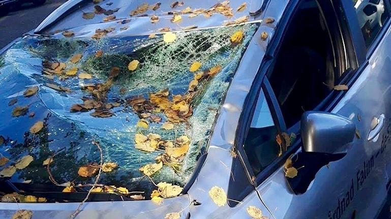 Ljusblå bil med krossad framruta och buckligt tak efter olycka.