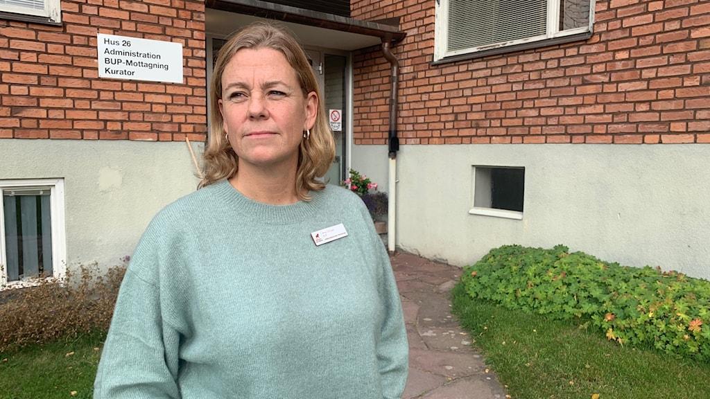 """En kvinna i ljusgrön tröja med namnskylt från Region Dalarna står framför en tegelbyggnad med skylt på väggen där det står """"Hus 26, Administration, BUP-Mottagning, Kurator""""."""