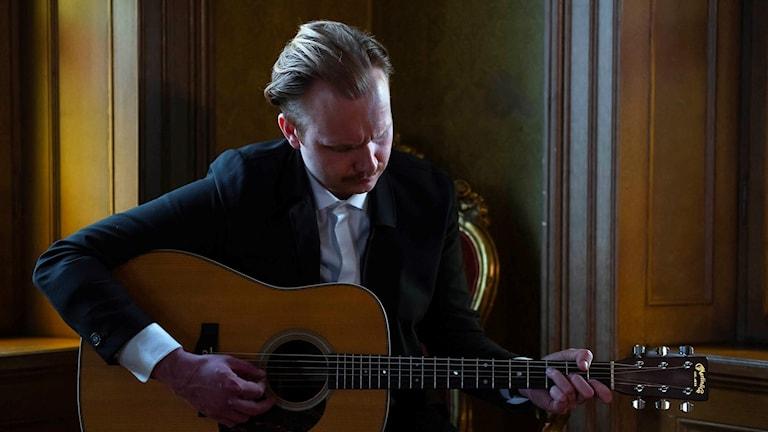 Artisten Broder Henrik Rapp med en gitarr.
