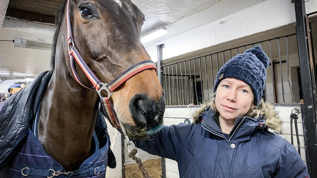 En kvinna som står bredvid en brun häst.