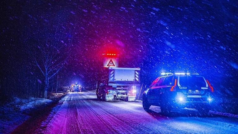 Sirener från ambulans och polisbil i mörkret.