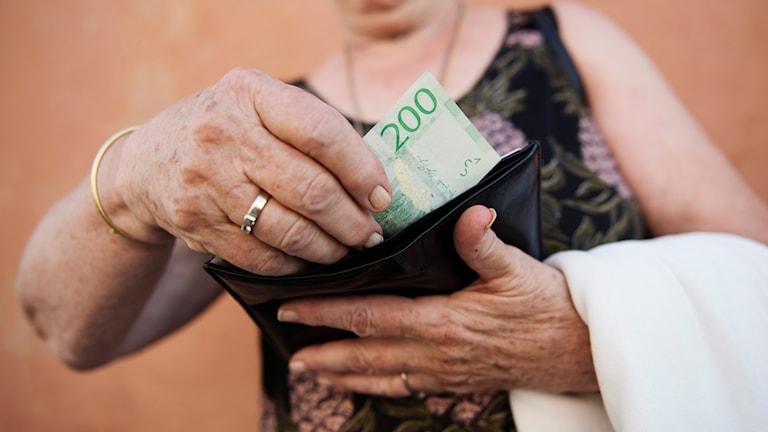 Äldre person tar upp en tvåhundrakronorssedel ur en plånbok.