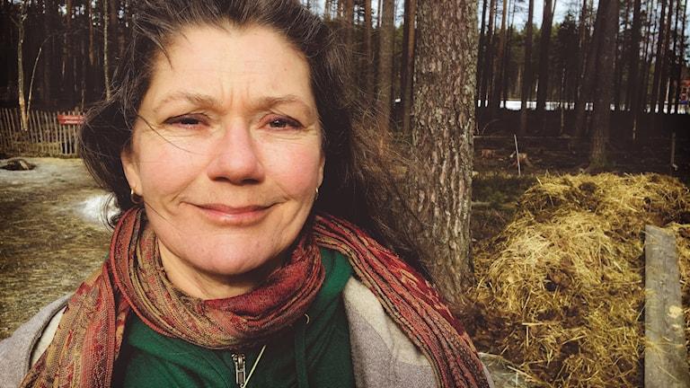 Miljöpartisten Maj Ardesjö i solsken, med en djurhage och skog i bakgrunden.