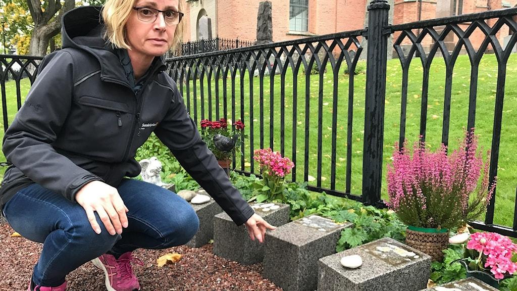Allvarlig kvinna med svart jacka som sitter vid gravplats utan namnbrickor.
