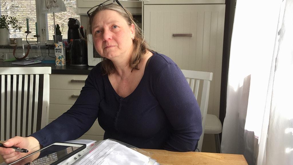 Kvinna sitter vid sitt köksbord.