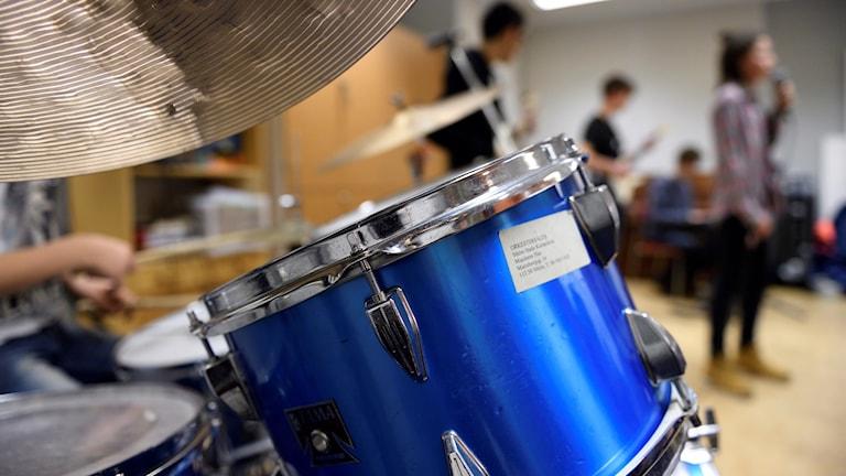 En person spelar trummor. Några personer sjunger och spelar gitarr i bakgrunden.