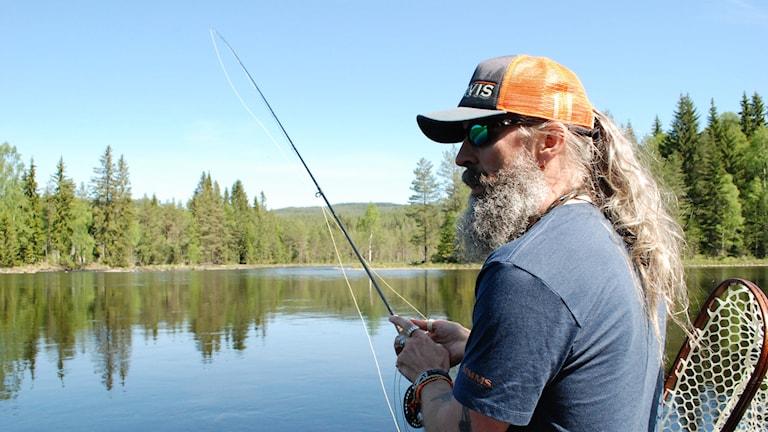 Fiskeguiden Stefan Larsson står med fiskespö i händerna vid ett vatten.