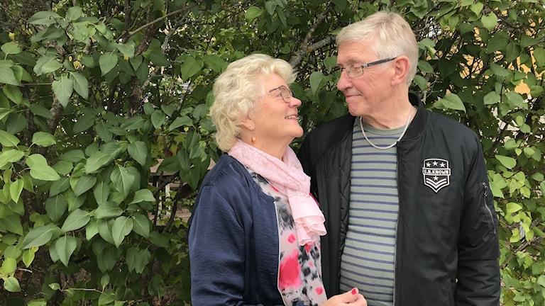 En äldre kvinna och en man står framför en buske och kollar på varandra.