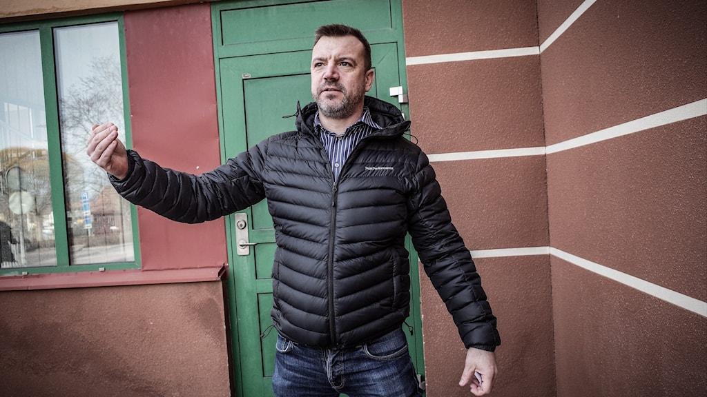 Man som står vid en grön dörr.