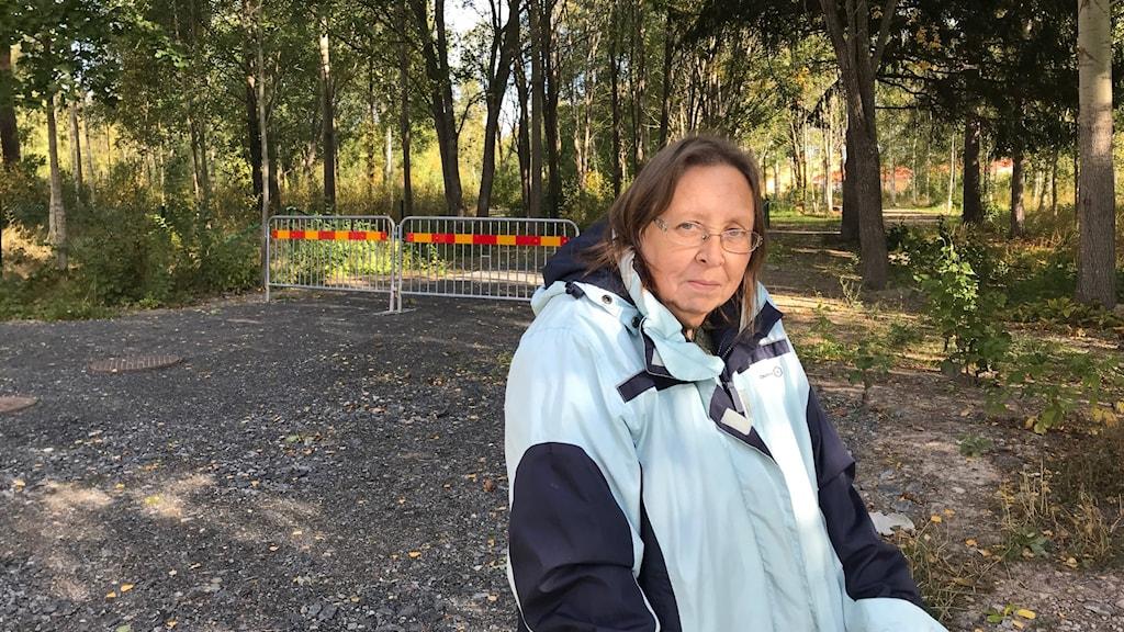 Kvinna vid en gång- och cykelväg i ett skogsområde.