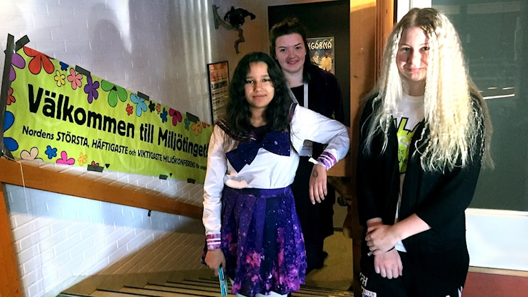 Tre tjejer i en trappa, i bakgrudnen en banderoll med texten Välkommen till Miljötinget.