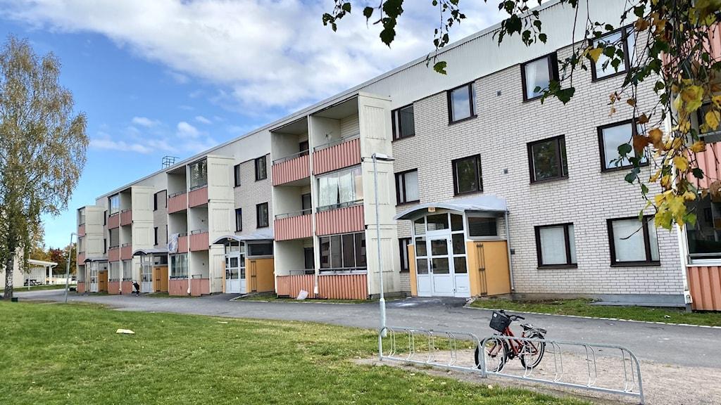Ett flerfamiljshus med tre vångar under en blå himmel.