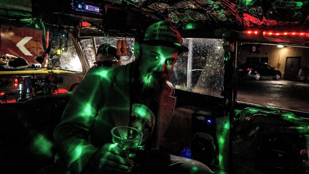 Man med grön belysning i ansiktet i en raggarbil.