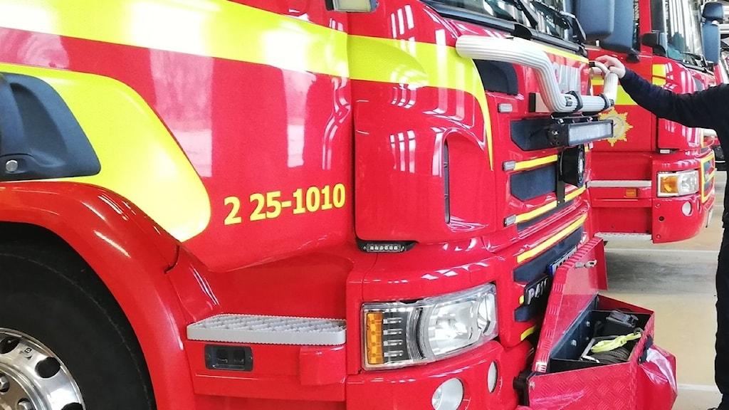 Räddningspersonal står framför ett av släckningsfordonen på Räddningstjänsten i Borlänge som ingår i förbundet Dala Mitt.
