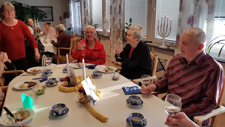 Flera äldre personer som sitter vid ett bord och äter