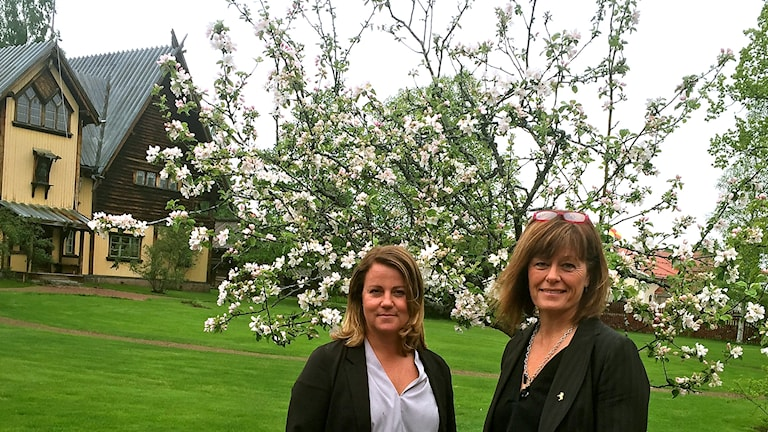 Bilden visar Jessica Åkerblom och Birgitta Bogren utomhus med blommande träd, ett gräs och ett hus i bakgrunden.