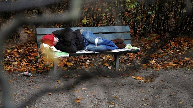 En hemlös man ligger och sover på en parkbänk.