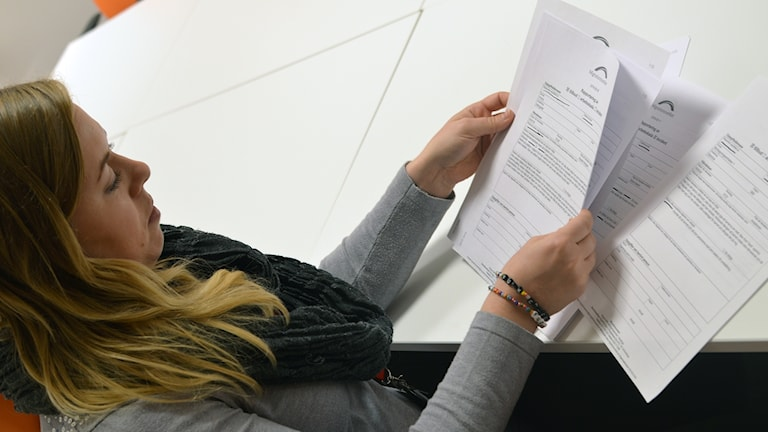 Jenny Andersson bläddrar bland Migrationsverkets incidentrapporter.