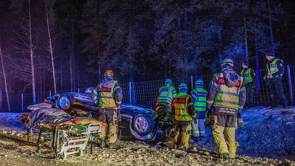Räddningsresurser står kring en bil som ligger på tak i diket.