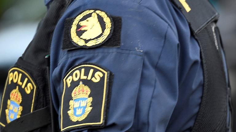 polis med hundföraremblem på uniformen