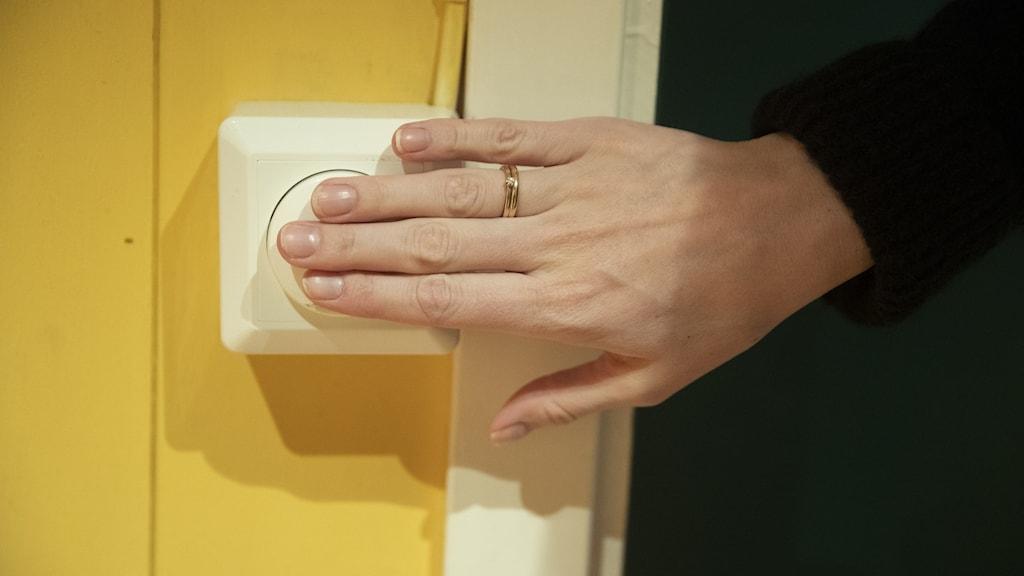 En hand som trycker på en strömbrytare.
